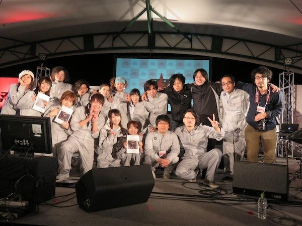 マチ★アソビ公演を終えた直後の記念写真。登壇者はお揃いの衣装を着ている。下段の一番右でピースサインをしているのが阿部さん、その左が横嶋監督だ。